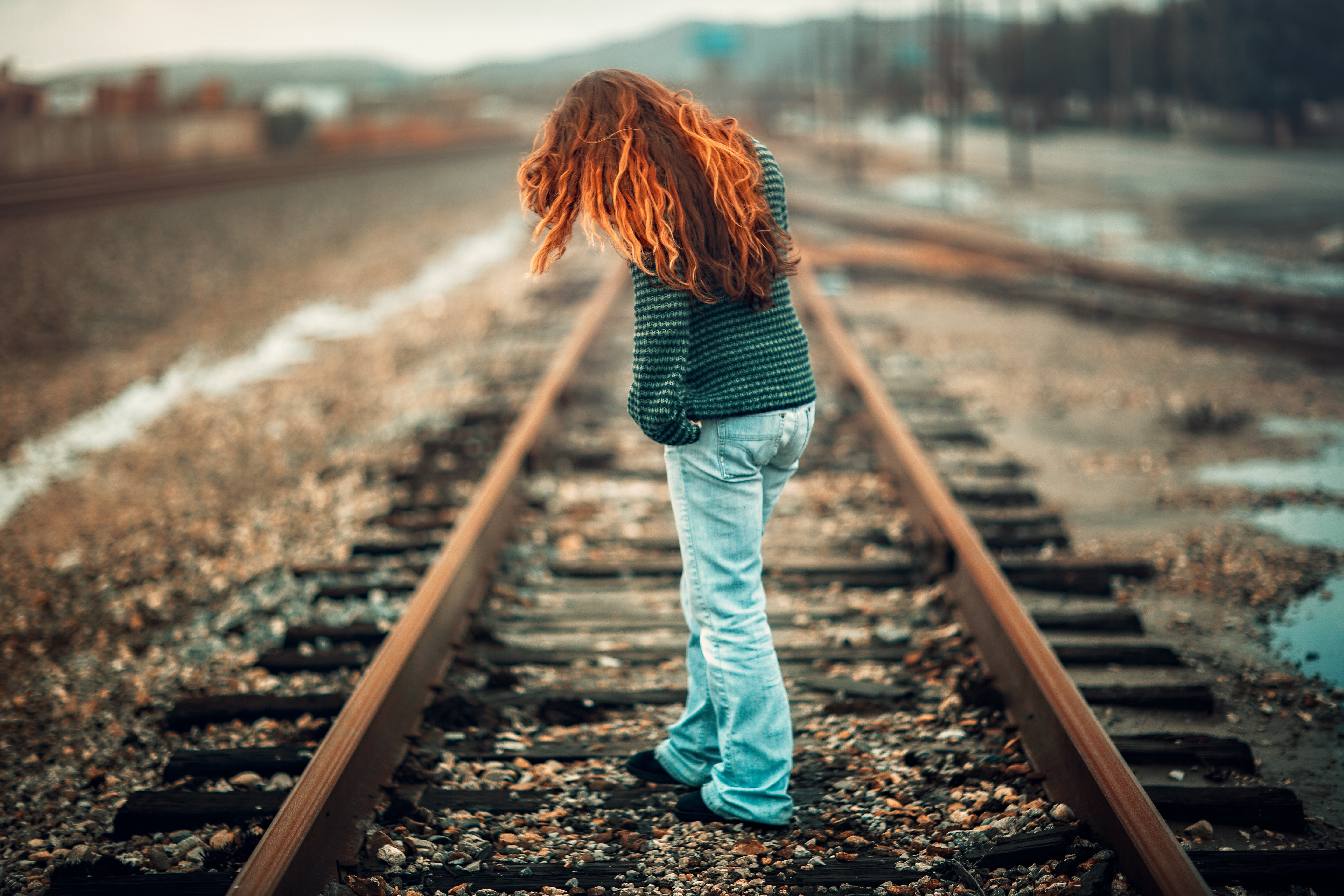 Red Haired Woman sad about her relationships, standing on the train tracks.