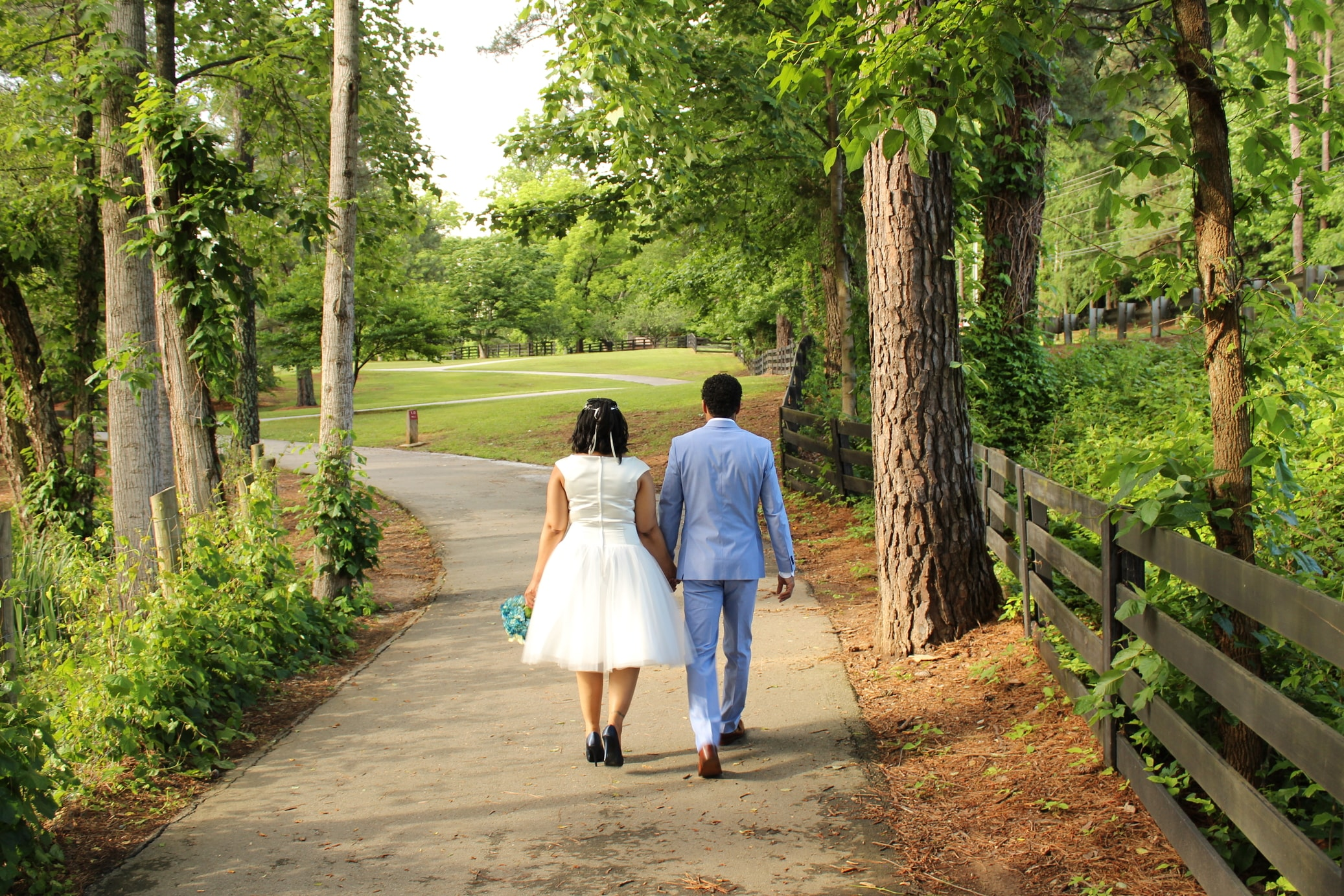 forsaking all others. African American couple holding hands, walking away through the forest.